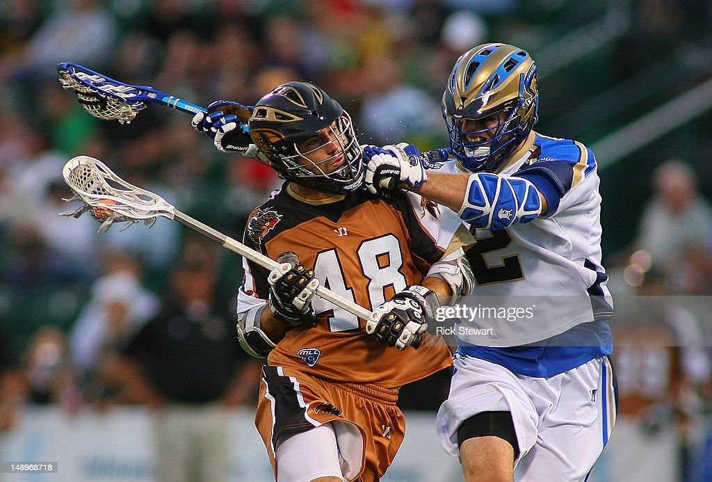 Roy Lang of the Rochester Rattlers is checked by Jeremy Boltus of the Charlotte Hounds at Sahlen's Stadium on July 20 2012 in Rochester New York