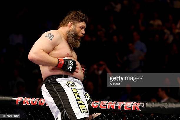 Roy Nelson sits on the side of the octagon in celebration of his win by knockout against Cheick Kongo of France in their heavyweight bout during the...