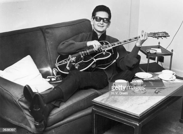 Roy Orbison American countrypop singer and songwriter strumming a guitar on the sofa of his room in the Westbury Hotel London
