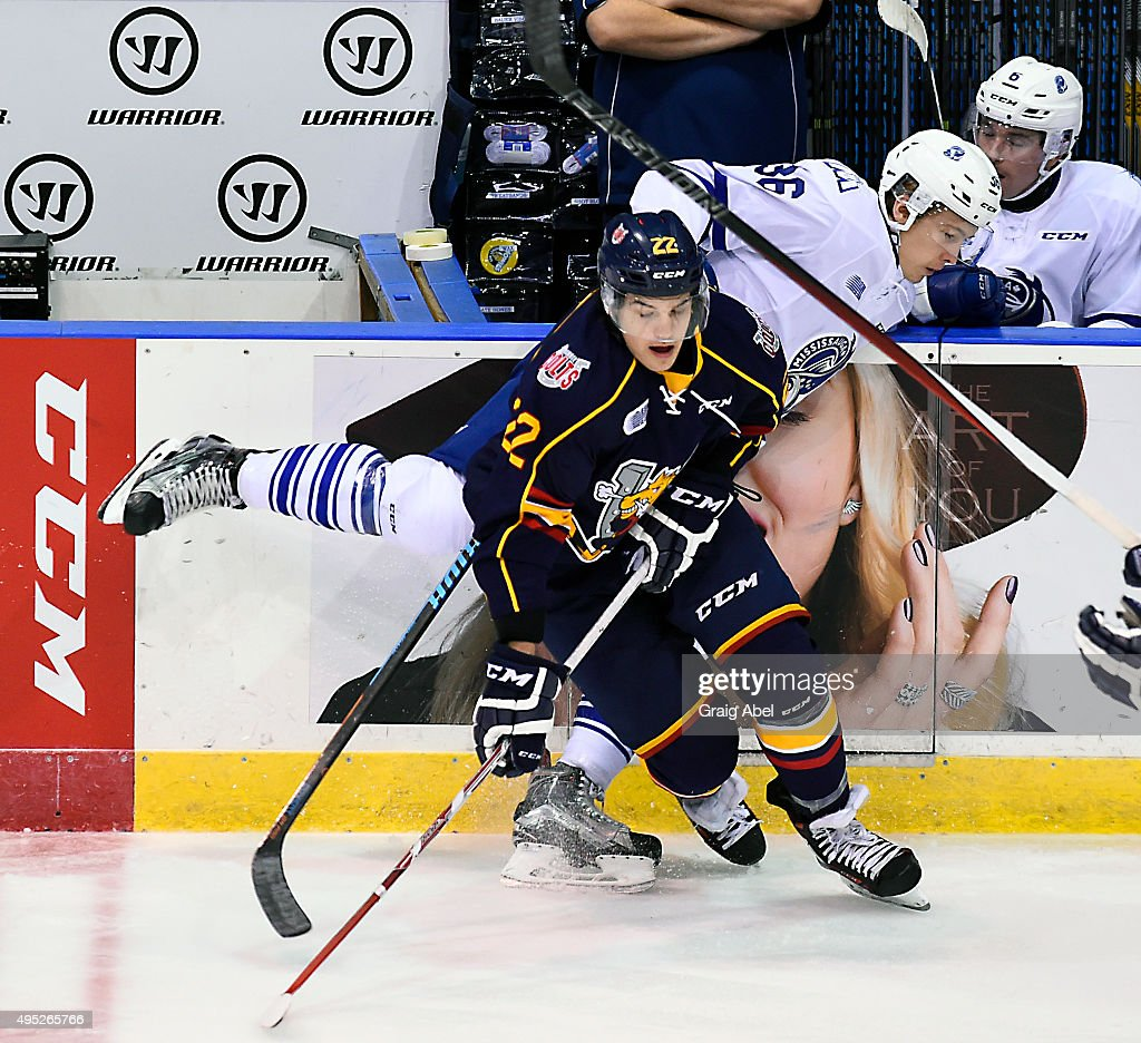 Roy Radke #22 of the Barrie Colts gets by a check from Austin Osmanski #36 of the Mississauga Steelheads during OHL game action on November 1, 2015 at the Hershey Centre in Mississauga, Ontario, Canada.