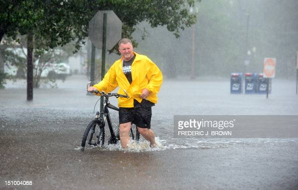 Roy Robertson pushes his bike in the rain through flooded streets in Slidell northeast of New Orleans on August 30 2012 in Louisiana Tropical Storm...