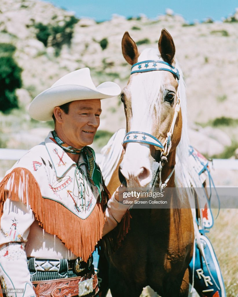 Roy Rogers US actor and singer wearing a white cowboy hat red neckerchief and fringed western shirt posing beside his palomino horse Trigger circa...