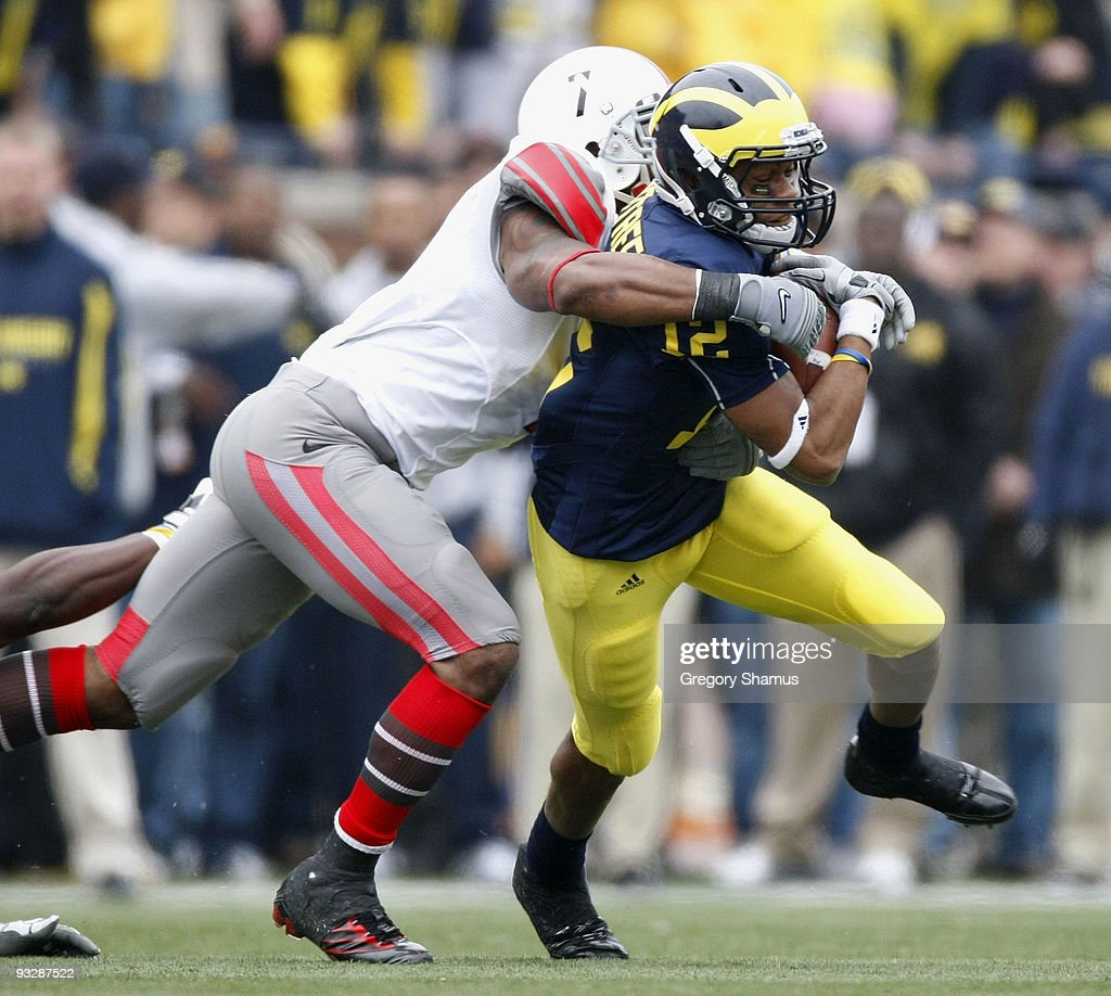Roy Roundtree #12 of the Michigan Wolverines tries to get though the tackle of Jermale Hines #7 of the Ohio State Buckeyes on November 21, 2009 at Michigan Stadium in Ann Arbor, Michigan. Ohio State won the game 21-10.