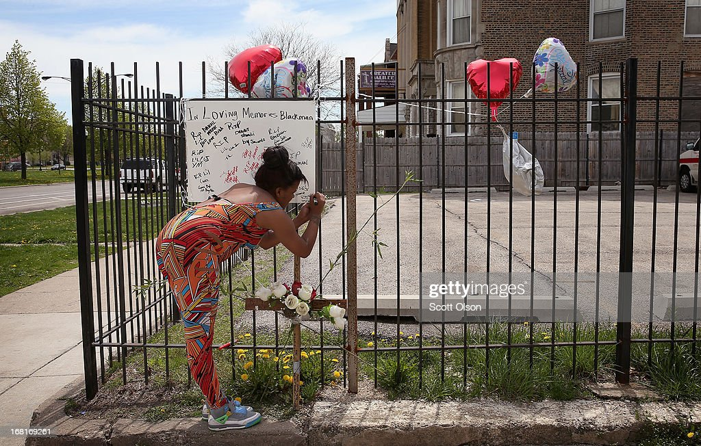 Roya Mitchell leaves a message on a memorial for her friend 16-year-old Tywon Jones near the spot where Jones was killed by police in front of the Greater Galilee Missionary Baptist Church on May 6, 2013 in Chicago, Illinois. According to police Jones was killed May 5 after he fired a pistol at police who were trying to stop him as he rode a bicycle away after shooting at a crowd of people moments earlier.