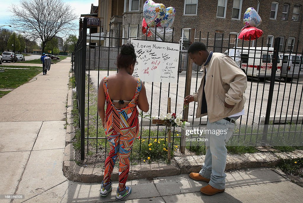 Roya Mitchell (L) writes a message on a memorial for her friend 16-year-old Tywon Jones as Jones' cousin Dion Jones places a cross near the spot where Tywon was killed by police in front of the Greater Galilee Missionary Baptist Church on May 6, 2013 in Chicago, Illinois. According to police Tywon was killed May 5 after he fired a pistol at police who were trying to stop him as he rode a bicycle away after shooting at a crowd of people moments earlier.