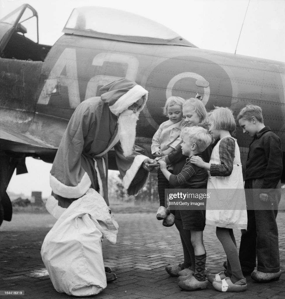 Fighter Command, Santa Claus (Leading Aircraftman Fred Fazan from London) hands out presents to Dutch children at Volkel, 13 December 1944. Members of No 122 Wing had saved their sweet ration for weeks, and contributed enough money to give the children their first proper Christmas party. It was noted by the photographer that this year Santa was afraid of Messerschmitts, so he decided to come by RAF Tempest!