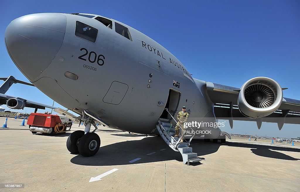Royal Australian Air Force flight technician Scott Taylor stands guard on the steps of a C-17 transport aircraft during the Australian International Airshow in Melbourne on March 1, 2013. 180,000 patrons are expected through the gates over the duration of the event staged at the Avalon Airfield some 80kms south-west of Melbourne. AFP PHOTO / Paul CROCK