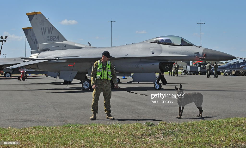 A Royal Australian Air Force security guard walks in front of an F-16 Fighting Falcon in the US Fighter compound during the Australian International Airshow in Melbourne on March 1, 2013. 180,000 patrons are expected through the gates over the duration of the event staged at the Avalon Airfield some 80kms south-west of Melbourne. AFP PHOTO / Paul CROCK