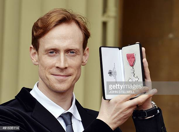Royal Ballet principal dancer Edward Watson poses with his medal after being appointed a Member of the Order of the British Empire for services to...