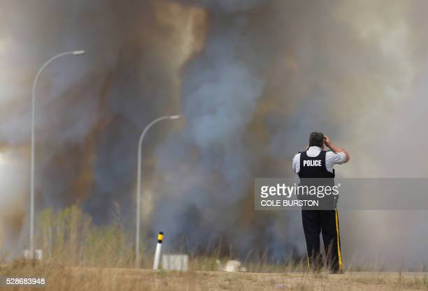 Royal Canadian Mounted Police look on as smoke rises from a forest fire along the highway near Fort McMurray Alberta on May 6 2016 Canadian police...