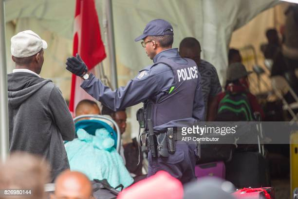 A Royal Canadian Mounted Police officer talks to migrants after they crossed the Canada/US border illegally near Hemmingford Quebec on August 6 2017...