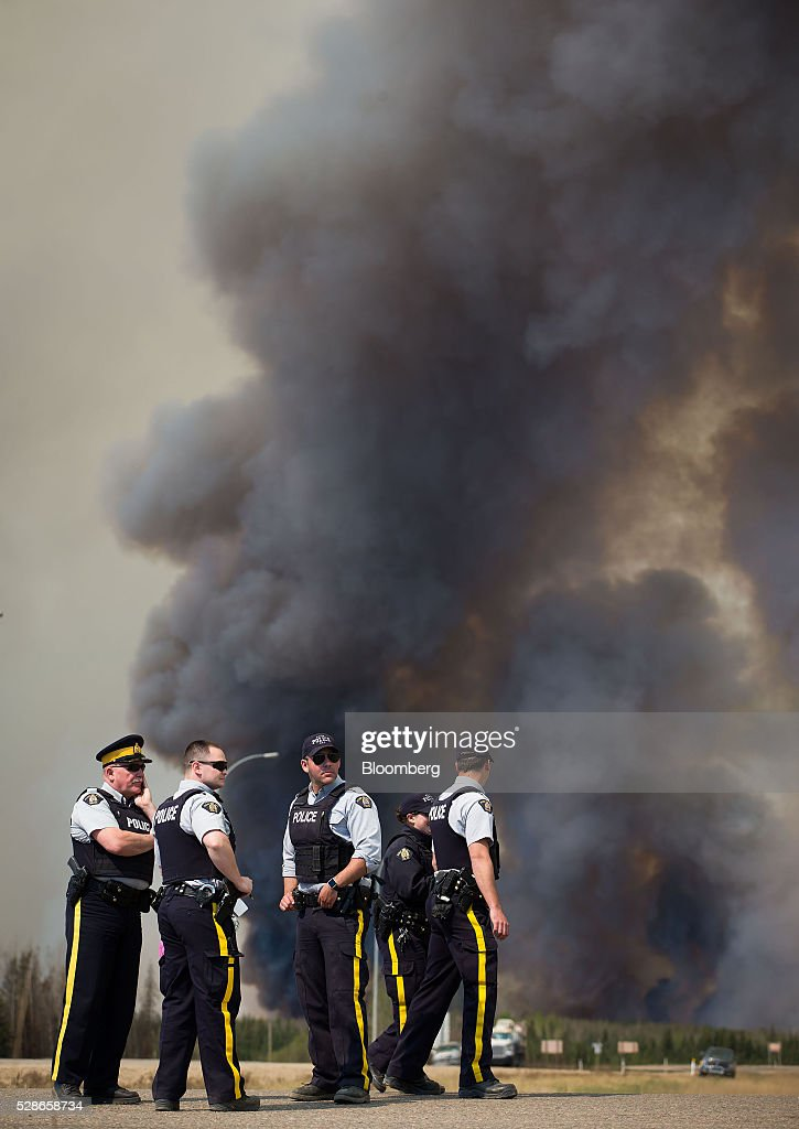 Royal Canadian Mounted Police (RCMP) officers stand at a roadblock as a wildfire burns south of Fort McMurray, Alberta, Canada, on Friday, May 6, 2016. The wildfires ravaging Canada's oil hub in northern Alberta have rapidly spread to an area bigger than New York city, prompting the air lift of more than 8,000 evacuees as firefighters seek to salvage critical infrastructure. Photographer: Darryl Dyck/Bloomberg via Getty Images
