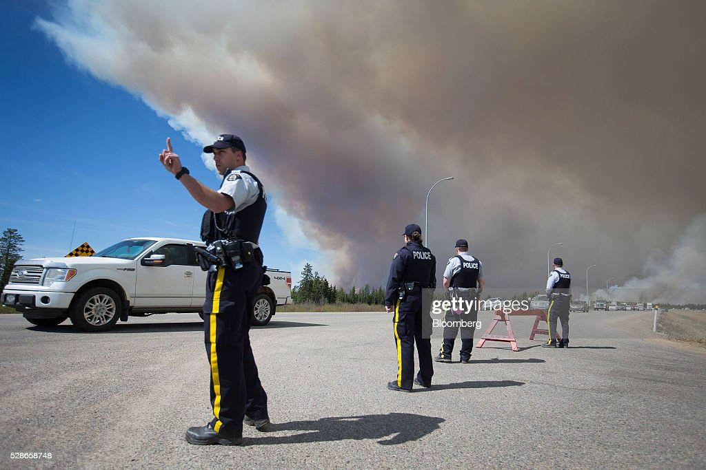 Royal Canadian Mounted Police (RCMP) officers stand at a roadblock as wildfire evacuees are escorted on Highway 63 near Anzac, Alberta, Canada, on Friday, May 6, 2016. The wildfires ravaging Canada's oil hub in northern Alberta have rapidly spread to an area bigger than New York city, prompting the air lift of more than 8,000 evacuees as firefighters seek to salvage critical infrastructure. Photographer: Darryl Dyck/Bloomberg via Getty Images