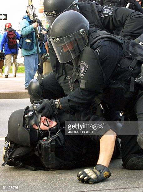 Royal Canadian Mounted Police tear the gas mask off a protester as they arrest him during a demonstration on the first day of the G20 meeting of...