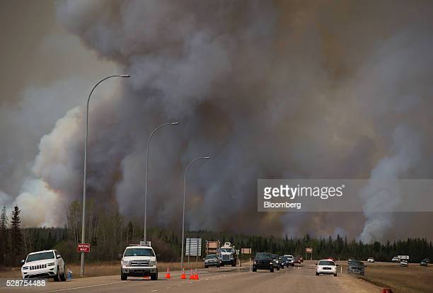 A Royal Canadian Mounted Police vehicle right escorts wildfire evacuees on Highway 63 near Anzac Alberta Canada on Friday May 6 2016 The wildfires...