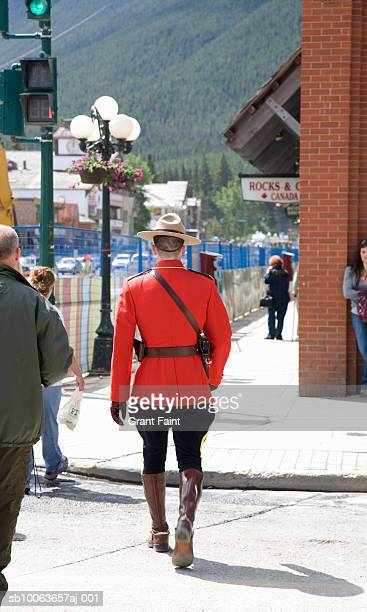 Royal canadian mounted police walking in street, rear view