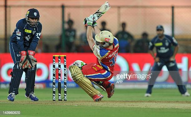 Royal Challengers Bangalore batsman AB DeVilliers looses grip while playing a shot while Deccan Chargers wicket keeper Parthiv Patel looks on during...