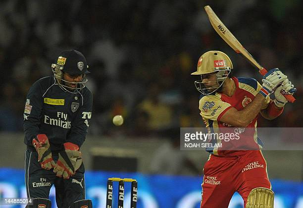 Royal Challengers Bangalore batsman Virat Kohli is watched by Deccan Chargers wicketkeeper Parthiv Patil as he plays a shot during the IPL Twenty20...