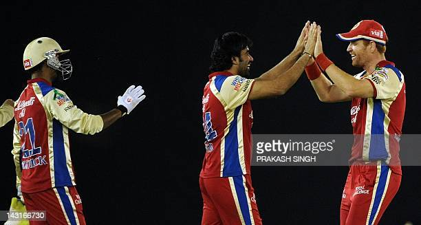 Royal Challengers Bangalore bowler Andrew McDonald celebrates taking the wicket of Kings XI Punjab batsman David Miller with Zaheer Khan and...