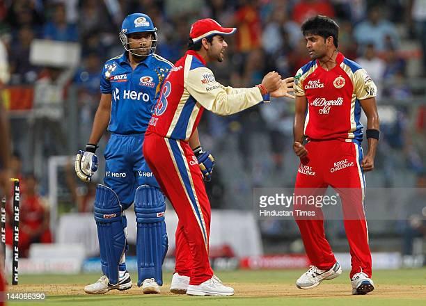 Royal Challengers Bangalore bowler Vinay Kumar celebrates with team captain Virat Kohli after the dismissal of Mumbai Indian batsman Rohit Sharma...