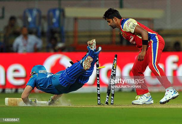 Royal Challengers Bangalore bowler Vinay Kumar runs out Pune Warriors batsman Steven Smith during the IPL Twenty20 cricket match between Royal...
