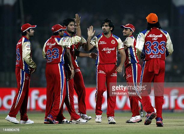 Royal Challengers Bangalore bowler Zaheer Khan celebrates with teammates after the dismissal of Delhi Daredevils batsman David Warner in IPL T20...