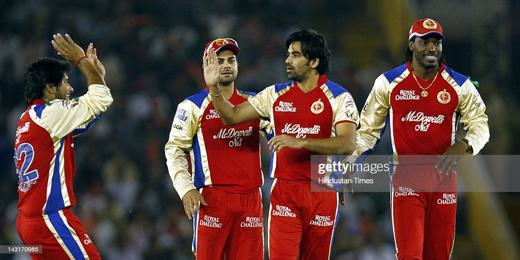 Royal Challengers Bangalore bowler <a gi-track='captionPersonalityLinkClicked' href=/galleries/search?phrase=Zaheer+Khan&family=editorial&specificpeople=217545 ng-click='$event.stopPropagation()'>Zaheer Khan</a> (2 R) celebrating with teammates Chris Gayle (R) and Virat Kohli (L) after the dismissal of Kings XI Punjab batsman Nitin Saini during IPL-5 T20 Cricket match played between Kings XI Punjab and Royal Challengers Bangalore at PCA stadium on April 20, 2012 in Mohali, India. Batting first after losing the toss Kings XI Punjab posted a target of 164 runs to win for Royal Challengers Bangalore.