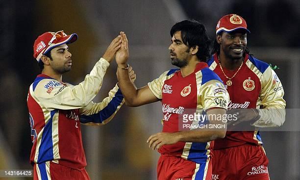 Royal Challengers Bangalore bowler Zaheer Khan Chris Gayle and Virat Kohli celebrate the dismissal of Kings XI Punjab batsman Paul Valthaty during...