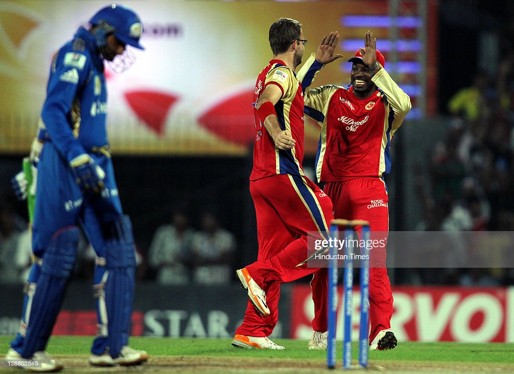 Royal Challengers Bangalore captain Daniel Vettori celebrates with teammate Chris Gayle after taking the wicket of Mumbai Indians captain Harbhajan...