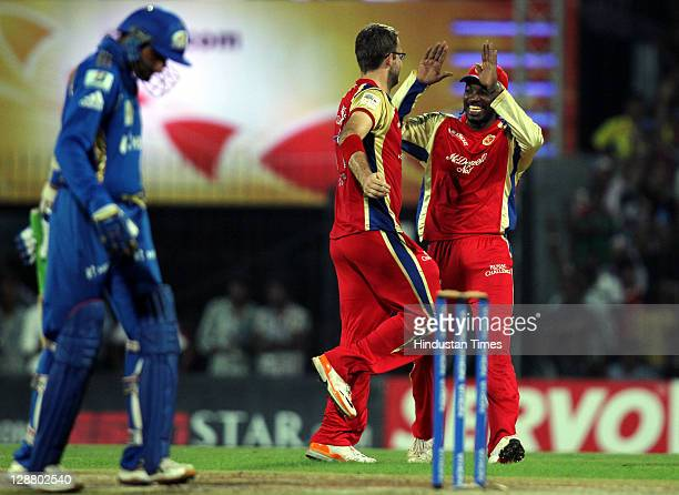 Royal Challengers Bangalore captain Daniel Vettori celebrates with teammate Chris Gayle after taking the wicket of Mumbai Indians captain Harbhajan...