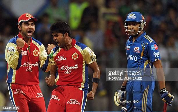 Royal Challengers Bangalore captain Virat Kohli celebrates with fast bowler Vinay Kumar after taking the wicket of Mumbai Indians batsman Rohit...