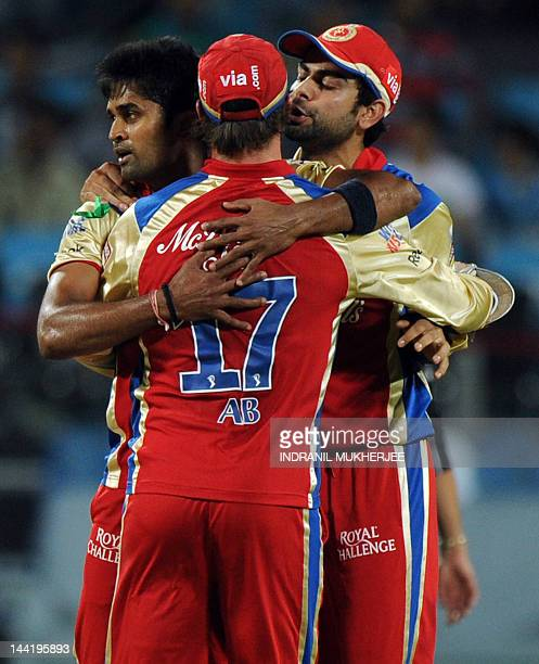 Royal Challengers Bangalore cricketer Vinay Kumar is congratulated by teammates AB De Villiers and Virat Kohli after taking the wicket of unseen Pune...