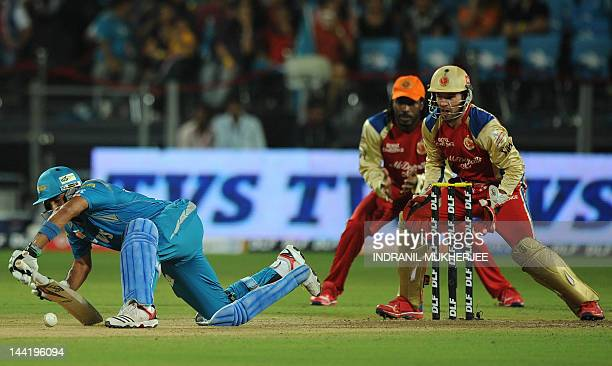 Royal Challengers Bangalore cricketers Chris Gayle and AB De Villiers watch as Pune Warriors India batsman Robin Uthappa loses his footing while...