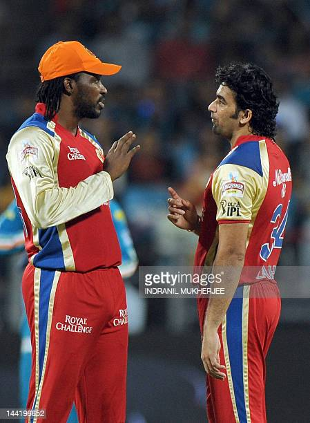 Royal Challengers Bangalore cricketers Chris Gayle and Zaheer Khan interact during the IPL Twenty20 cricket match between Pune Warriors India and...