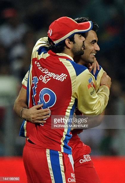 Royal Challengers Bangalore cricketers Virat Kohli and Zaheer Khan celebrate after the wicket of unseen Pune Warriors batsman Anustup Majumdar during...