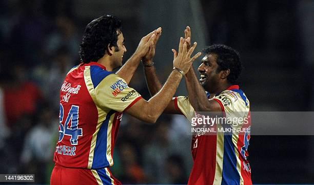 Royal Challengers Bangalore cricketers Zaheer Khan and Muttiah Muralitharan celebrate the wicket of unseen Pune Warriors India batsman Robin Uthappa...