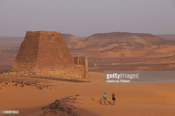 Royal city of Meroe, ancient capitol of Kushite Kingdom and Royal Cemetery also known as al Ahram or 'the pyramids' with tourist couple heading towards pyramid, Meroe, Shendi, Sudan