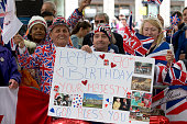 A royal fan hold up a birthday card for Britain's Queen Elizabeth II on it ahead of a service of thanksgiving for the Queens 90th birthday at St...
