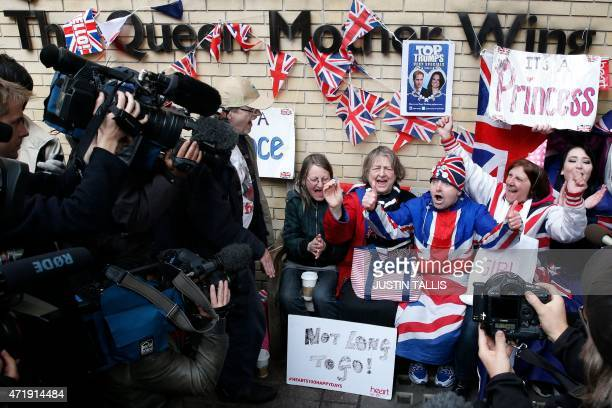 Royal fans are surrounded by media as they celebrate following the announcement of the birth of Catherine Duchess of Cambridge and Prince William's...