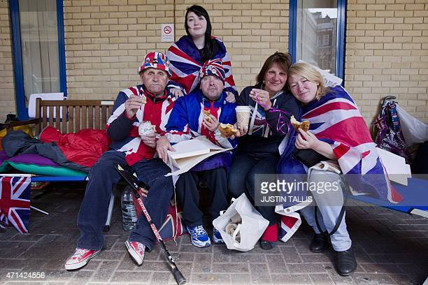 Royal fans pose eating pastries given to them by the Royal couple outside the Lindo Wing of St Mary's hospital in central London on April 28 2015 The...