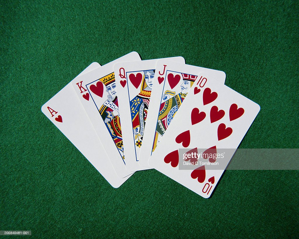 Royal flush hand of cards, hearts suit, on playing baize, close-up : Stock Photo