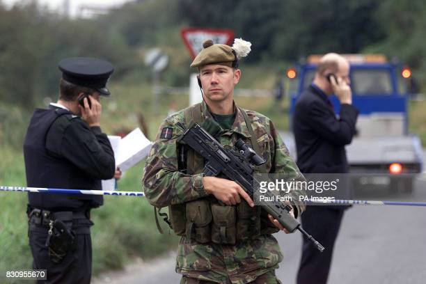 A Royal Highland Fusilier and police officers seal off a border road near Newry Co Down where two unexploded undercar boobytrap bombs were discovered...