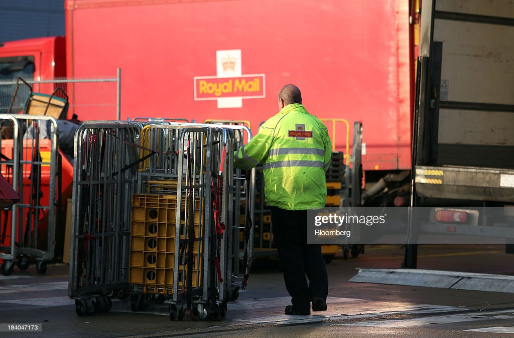 A Royal Mail Group Ltd. employee loads trolleys on to a van at the company's postal sorting office in Romford, U.K., on Friday, Oct. 11, 2013. Royal Mail Group Ltd., Britain's 360-year-old postal service, jumped as much as 38 percent on its trading debut, heightening criticism of an initial public offering that opposition politicians say was underpriced. Photographer: Chris Ratcliffe/Bloomberg via Getty Images