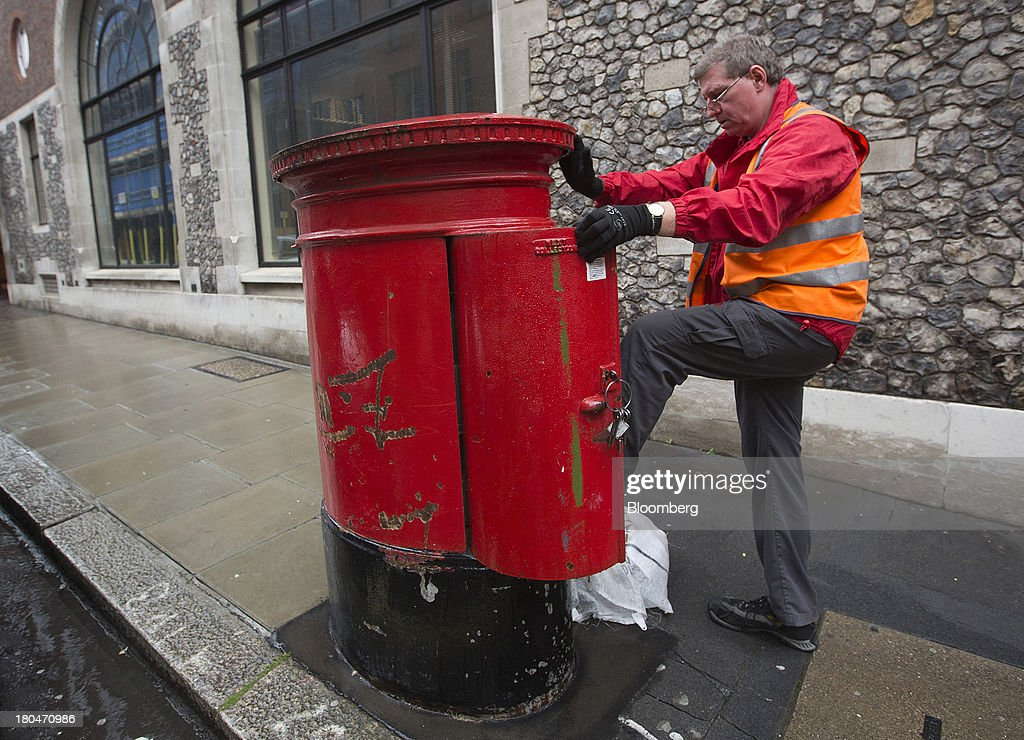 A Royal Mail Group Ltd. employee opens a pillar box as he collects post in London, U.K., on Friday, Sept. 13, 2013. Royal Mail Group Ltd., the U.K.'s 360-year-old postal service, intends to hold an initial public offering of a majority stake 'in the coming weeks' to help the company gain a competitive edge against European rivals. Photographer: Simon Dawson/Bloomberg via Getty Images