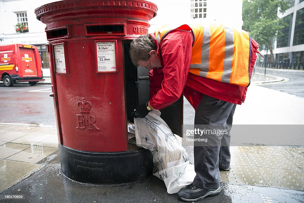 A Royal Mail Group Ltd. employee places post into a sack as he makes a collection from a double aperture pillar box in London, U.K., on Friday, Sept. 13, 2013. Royal Mail Group Ltd., the U.K.'s 360-year-old postal service, intends to hold an initial public offering of a majority stake 'in the coming weeks' to help the company gain a competitive edge against European rivals. Photographer: Simon Dawson/Bloomberg via Getty Images