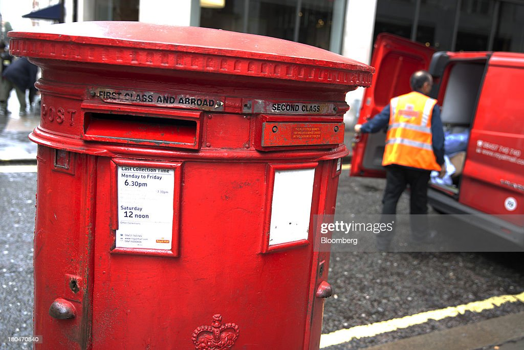 A Royal Mail Group Ltd. employee places sacks of post into the back of a mail truck after collecting from a double aperture pillar box in London, U.K., on Friday, Sept. 13, 2013. Royal Mail Group Ltd., the U.K.'s 360-year-old postal service, intends to hold an initial public offering of a majority stake 'in the coming weeks' to help the company gain a competitive edge against European rivals. Photographer: Simon Dawson/Bloomberg via Getty Images