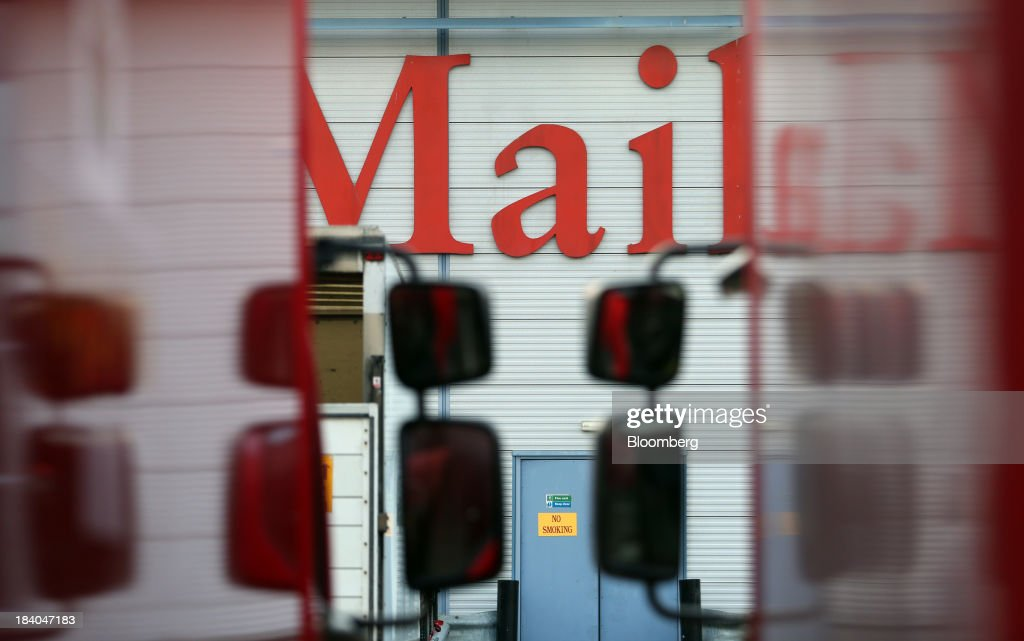 A Royal Mail Group Ltd. logo sits above delivery trucks at the company's postal sorting office in Romford, U.K., on Friday, Oct. 11, 2013. Royal Mail Group Ltd., Britain's 360-year-old postal service, jumped as much as 38 percent on its trading debut, heightening criticism of an initial public offering that opposition politicians say was underpriced. Photographer: Chris Ratcliffe/Bloomberg via Getty Images