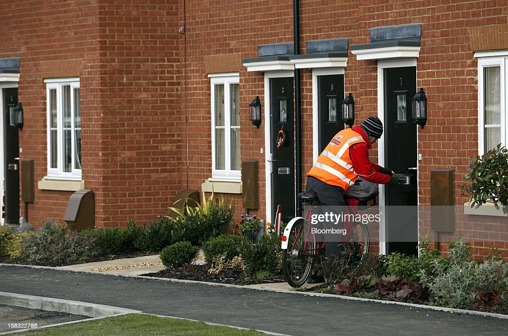 A Royal Mail Group Ltd. postman delivers letters to completed homes at a Barratt Developments Plc construction site for residential housing in Bedford, U.K., on Thursday, Dec. 13, 2012. Barratt Developments Plc, the U.K.'s largest homebuilder by volume, said advance sales rose 21 percent as government initiatives to boost homebuilding lifted private reservations in the autumn selling season. Photographer: Chris Ratcliffe/Bloomberg via Getty Images