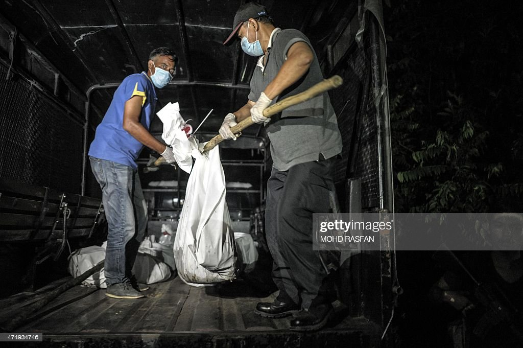 Royal Malaysian Police carry exhumed human remains into a police truck after being recovered from the jungle in the Malaysian northern state of...