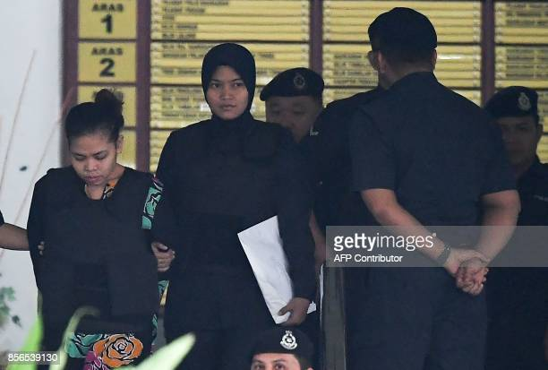 Royal Malaysian Police escort Indonesian defendant Siti Aisyah after her trial at the Shah Alam High Court in Shah Alam outside Kuala Lumpur on...
